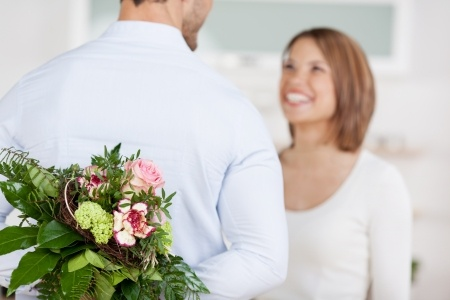 21162486 - young man hides a bouquet of flowers behind his back